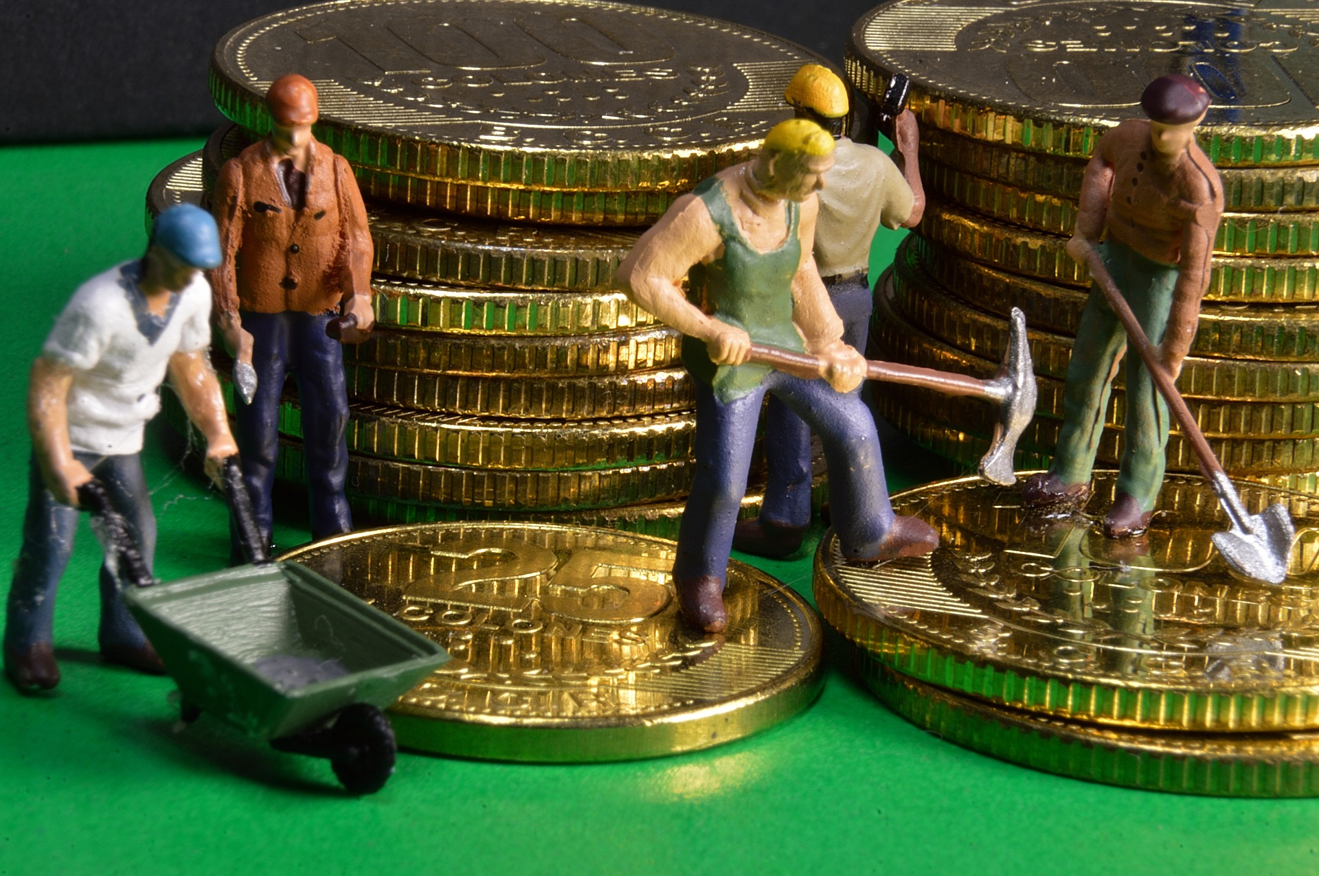 figurines of workers standing on coin pile